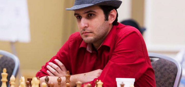 GM Elshan Moradi sits at a chess board wearing a red shirt and a grey fedora